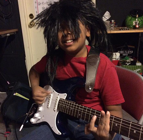 Young Boy Smiling With Electric Guitar
